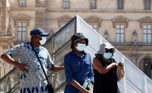 Tres personas con mascarilla, para protegerse del coronavirus, cerca del Museo del Louvre, en París.
