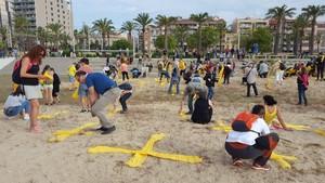 Cruces hechas con toallas amarillas en la playa de Mataró.