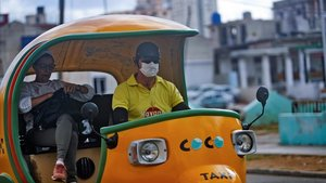 Un chófer de cocotaxi usa mascara como medida de proteccion contra el coronavirus este lunes en La Habana (Cuba).