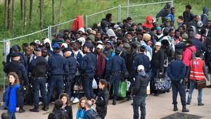 Policías franceses escoltan a los refugiados que han sido desalojados del campamento cercano a París.