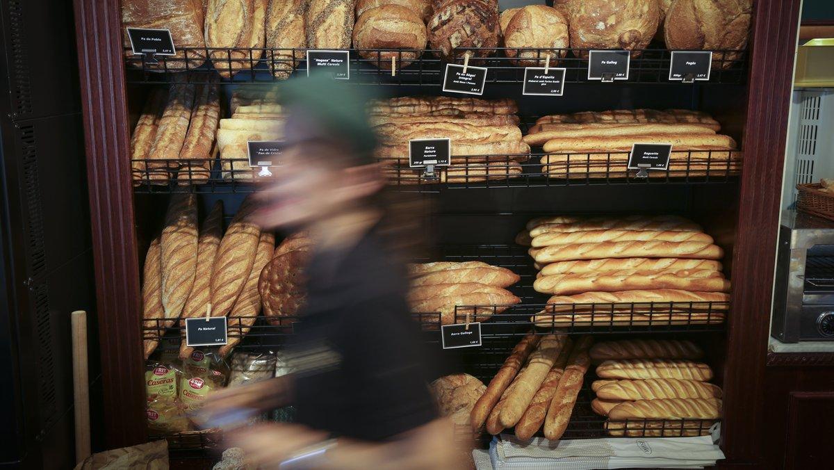 Un trabajador de un horno de pan despachando a los clientes.