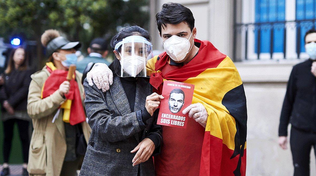 Dos jóvenes posancon un folleto irónico contra Pedro Sánchez durante la protesta de los residentes del barrio de Salamanca de Madrid contra la gestión de la crisis del coronavirus por parte del Gobierno, el 14 de mayo.