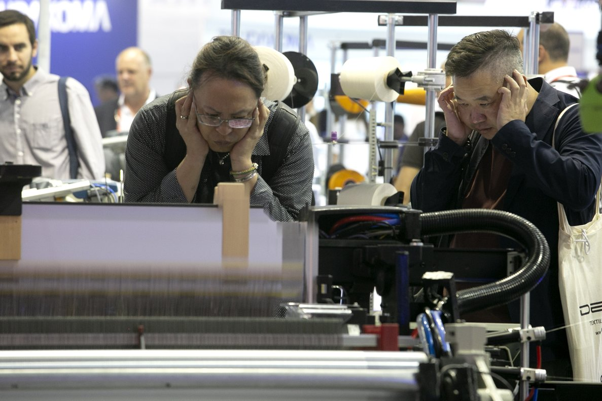 Visitantes de la feria ITMA 2019 se protejen los oídos ante el fragor de las máquinas en funcionamiento.