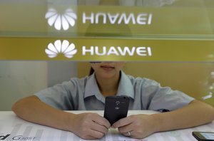 A sales assistant looks at her mobile phone as she waits for customers behind a counter at a Huawei booth in Wuhan, Hubei province, October 10, 2012. REUTERS/Stringer/File Photo CHINA OUT. NO COMMERCIAL OR EDITORIAL SALES IN CHINA