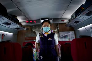 FILE PHOTO: A train staff member walks on a high-speed train at Wuhan Railway Station, in Wuhan, the Chinese city hit the hardest by the coronavirus disease (COVID-19) outbreak, in the Hubei province, China, May 17, 2020. REUTERS/Aly Song/File Photo