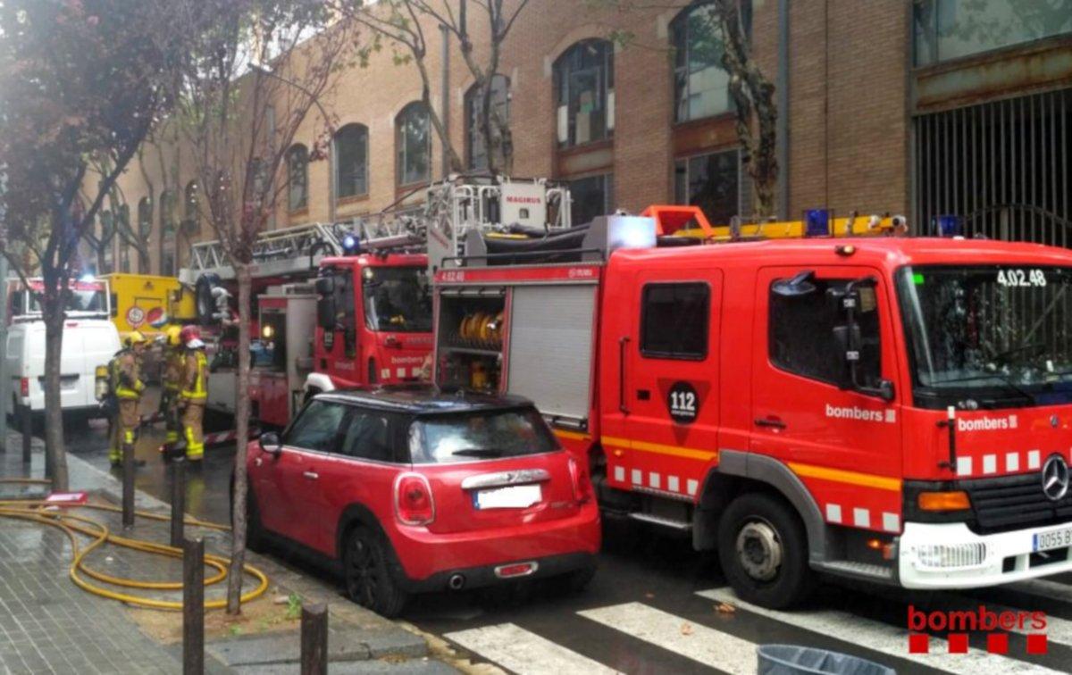 Plan general de dos camiones de los Bomberos de la Generalitat durante la actuación para apagar un incendio en un bloque de pisos de Sant Roc.