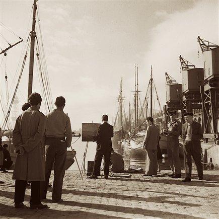 Los viejos veleros eran embarcaciones recurrentes del puerto durante los años 40 y 50. La guerra había destruido los grandes barcos y la posguerra construía poco, así que las viejas naves no se desballestaban, seguían haciendo transporte de cabotaje. La imagen muestra el Moll d'Espanya, donde actualmente se levanta el Maremagnum.