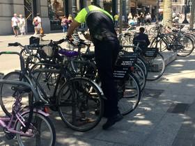 Un agente de la Guardia Urbana fotografía una de las bicis de Donkey Republic, el miércoles, en la plaza de Catalunya.