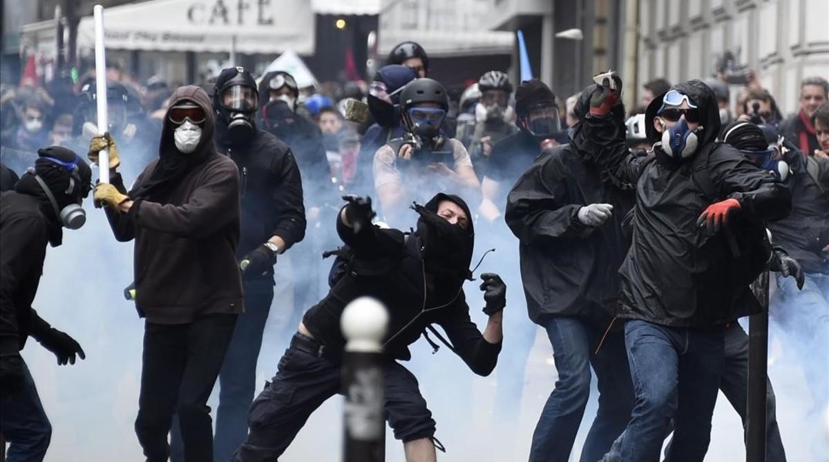 Un grupo de encapuchados lanza objetos contra la policía en París, el 14 de junio.