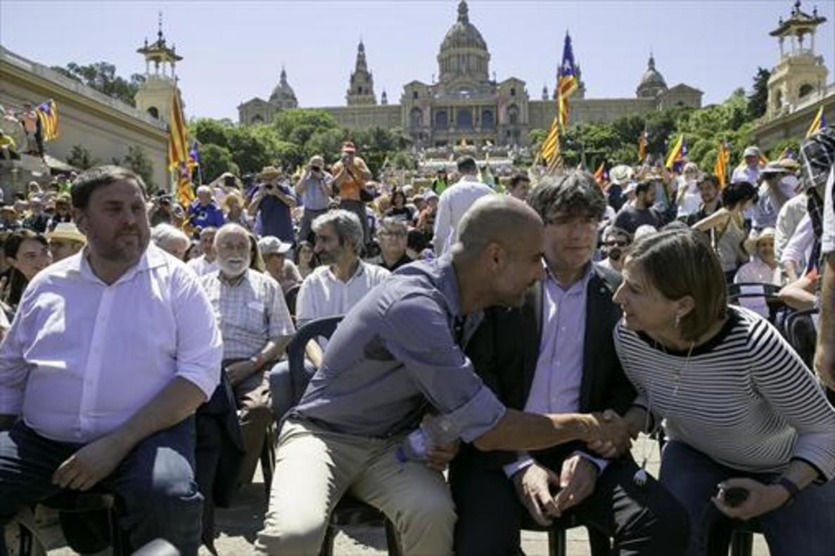 Guardiola saluda a Forcadell en presencia de Puigdemont y Junqueras, en el acto de Montjuïc en el que actuó como portavoz soberanista.