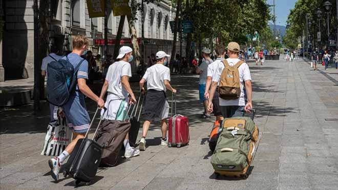 El IPC cae un 0,4 % en septiembre y encadena seis meses de tasas negativas. En la foto, turistas con sus maletas en el centro de Barcelona, en junio pasado.