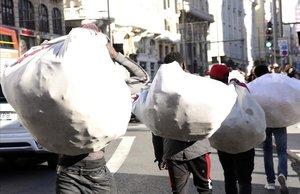 Un grupo de manteros se dirige hacia sus posiciones en la Gran Vía de Madrid.