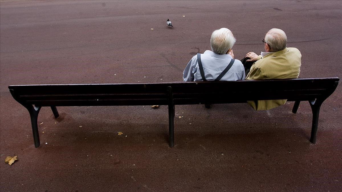 Dos hombres mayores charlan en un banco, en Barcelona.