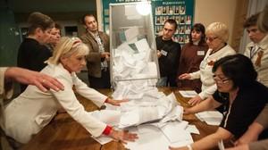 Miembros del comité electoral vacían una urna para hacer el escrutinio tras la votación en Donetsk.