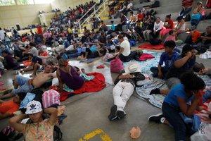 Migrantes hondureños descansan en un refugio