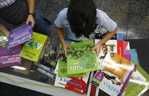 Dos niñas revisan unos libros de texto depositados sobre una mesa.