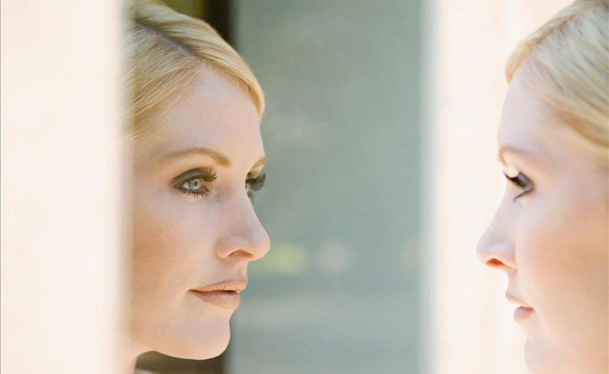 Mujer joven frente al espejo.