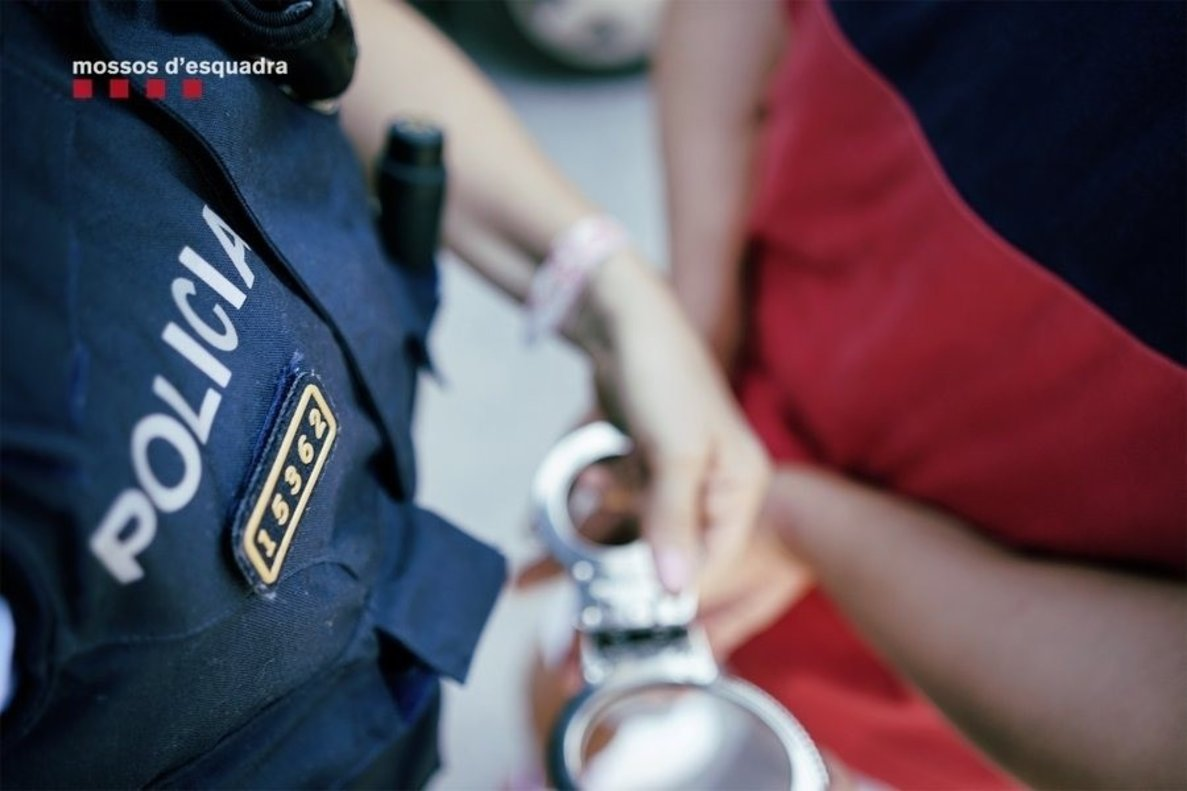 Un policía pone las esposas a un detenido.