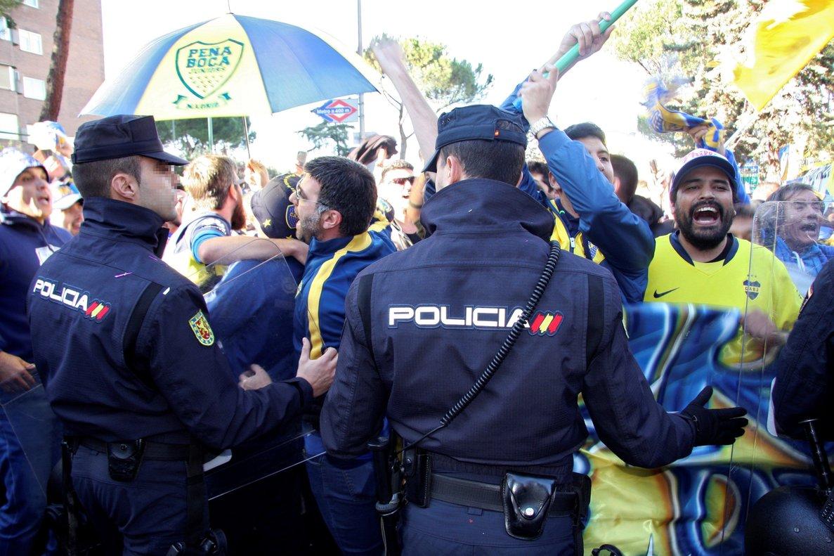 Agentes de la Policía Nacional vigilan a aficionados de Boca, en Madrid.