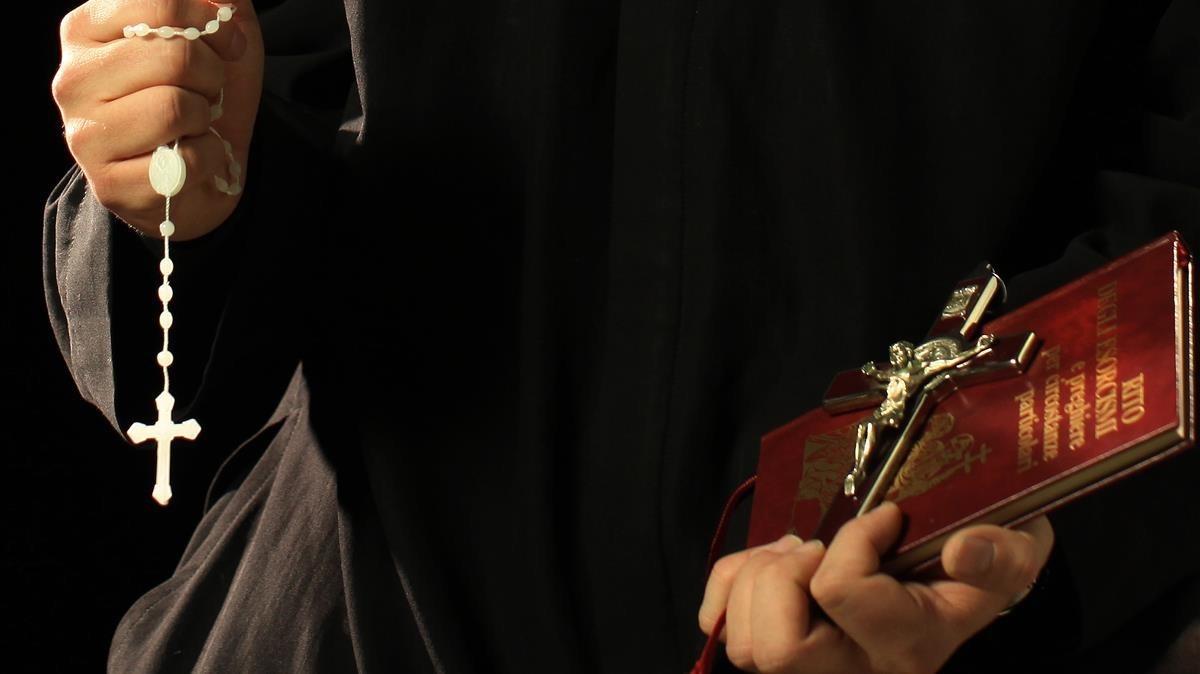 Un sacerdote, sostiene la bliblia y un rosario.