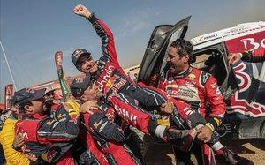 Stéphane Peterhanse 'Mister Dakar' y Nasser Al-Attiyah levantan a un triunfador Carlos Sainz, hoy, en Arabia Saudí.