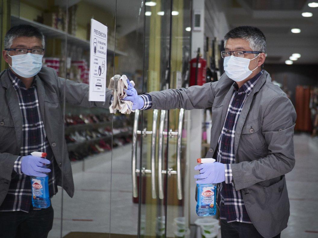Un hombre desinfecta la puerta de entrada de su tienda de ropa tras reabrirla.