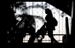 Una madre camina empujando el cochecito de su hijo por una estación de tren.