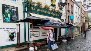 Una mujer con mascarilla pasa por una céntrica calle de Dublín.