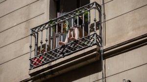 Una mujer disfruta del sol desde su balcón, en un edificio de Barcelona, el 12 de mayo.