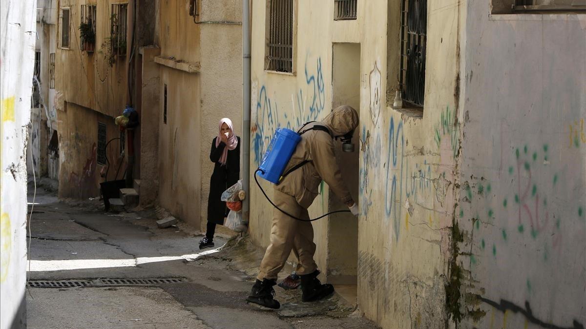 Una mujer palestina cubre su cara con un pañuelo mientras un trabajador de protección civil desinfecta un portal, el pasado día 16 de marzo.