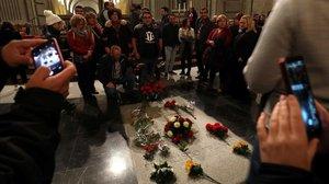 Varios ciudadanos posan ante la tumba de Franco en el Valle de los Caídos, este sábado.
