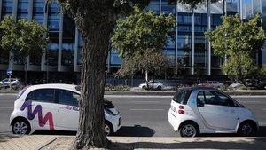 Vehículos de Emov y car2go aparcados en una calle de Madrid