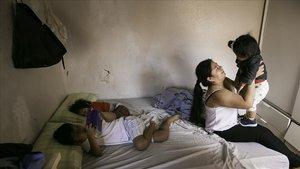 Marlene Marcos, junto a sus dos hijos Eydan (8 años) y Laia (3 años), sostiene lahija de una amiga para que la madre pueda ir a trabajar.