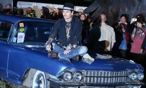 El actor estadounidense Johnny Depp, posando sobre un coche, esta noche en el festival de Glastonbury, en Inglaterra.