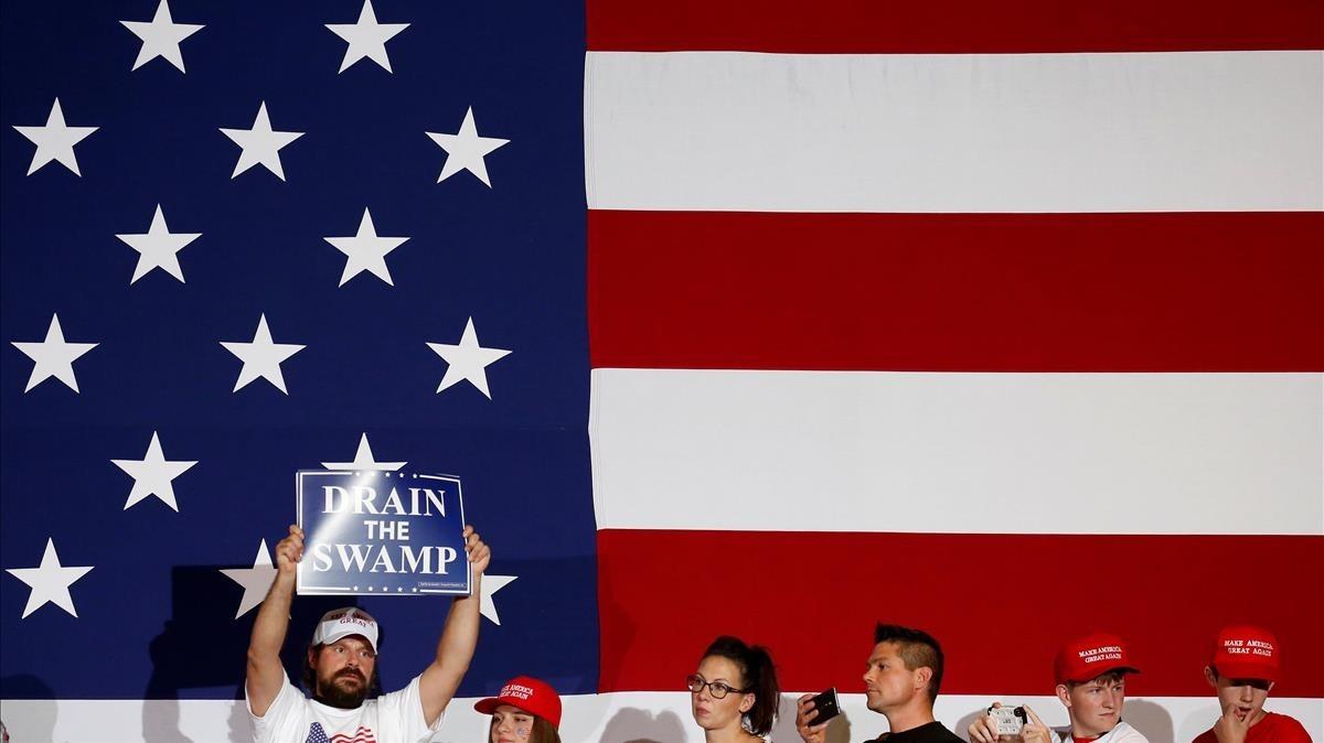 Apoyadores de Donald Trump en frente de la bandera estadounidense durante un mitín en la campaña electoral de 2016
