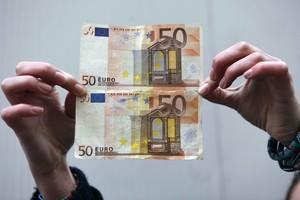 Un billete de 50 euros bueno (arriba) y otro falsificado (el de abajo).