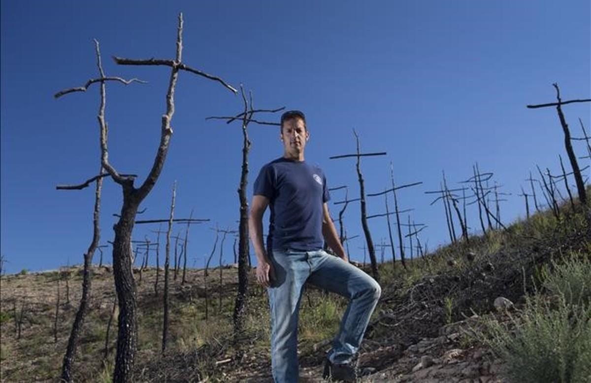 El bombero y artista Marc Sellarès en el bosque de cruces que ha creado en la zona del incendio de Ódena.