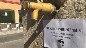 BROMA Y DENUNCIA. Un cartel promociona homeopatía gratis en una fuente de agua corriente.