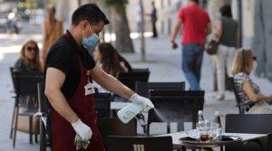 Un camarero desinfecta una mesa de una terraza, el 29 de julio.