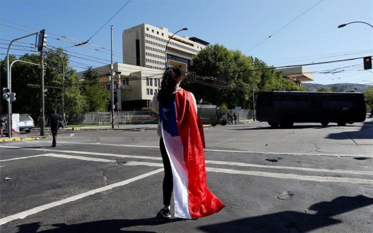 Una mujer con la bandera de Chile observa los bloqueos militares.