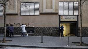 Un trabajadorborra la aparición de la palabra culpables sobre la fachada del colegio de Les Corts.