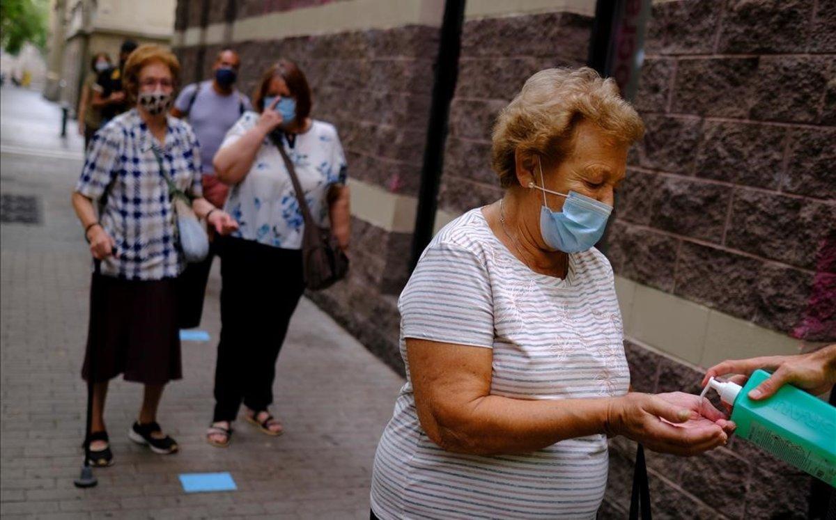 Una mujer se lava con gel hidroalcohólico antes de realizarse un test PCR en el Raval, Barcelona.