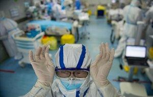 Una infermera se ajusta las gafas antes de empezar a trabajar con pacientes del coronavirus en un hospital en Wuhan, China.