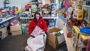 Una voluntaria de la Cruz Roja, con regalos de la entidad para ayudar a los Reyes a llevar regalos a todos los niños.