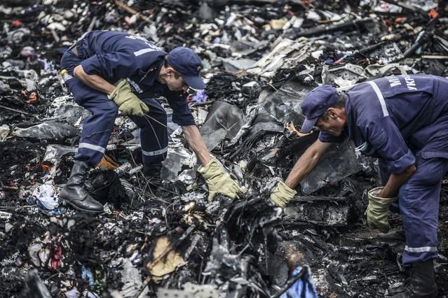 Dos agentes buscan entre los restos del vuelo MH17 de Malaysia Airlines, el pasado 20 de julio en Donetsk (Ucrania).