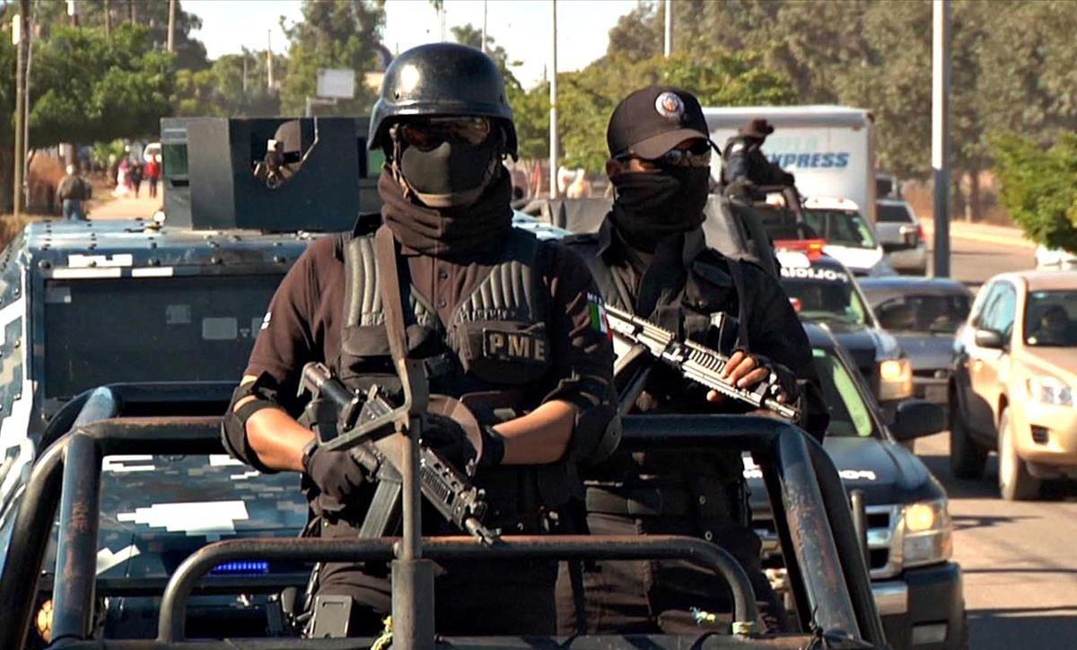Dos agentes de la policía mexicana en un convoy de seguridad.
