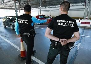 Dos guàrdies civils paren un cotxe a la duana de la Farga de Moles.