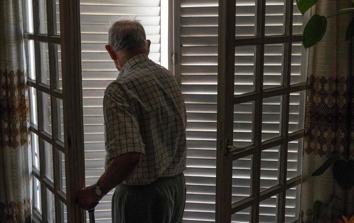 Un hombre cierra los porticones de una ventana para resguardarse del sol en Clemont-Ferrand (Francia).
