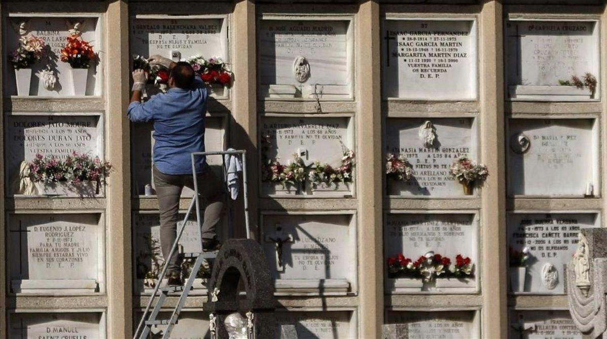 Un hombre sobre una escalera en un cementerio.