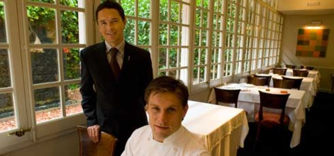 Joan Junyent (de pie) con el chef Carlos Alconchel, en las mesas del Windsor que dan al jardín. Foto: JOAN PUIG